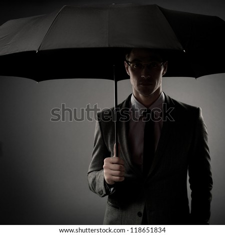 Businessman in costume holding black umbrella