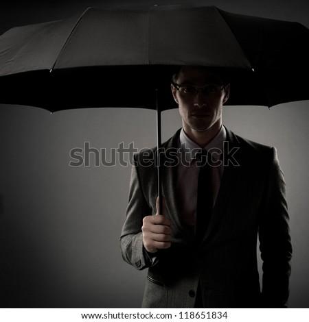Businessman in costume holding black umbrella - stock photo