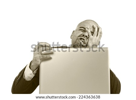 businessman in crisis and stress at computer laptop holding monitor watching online finances drop down or loosing money internet gambling isolated on white background - stock photo