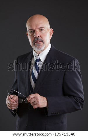 businessman in dark blue suit holding glasses