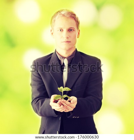 Businessman in dark suit holding smal plant in his hands - growth concept - stock photo