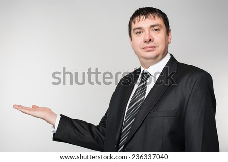 Businessman in dark suit holds out his hand flat isolated on white background - stock photo
