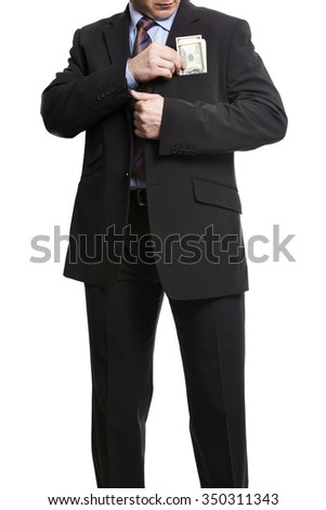 Businessman in dark suit puts a bunch of American Dollars into jacket pocket. Isolated on white background.