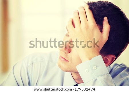 Businessman in depression with hand on forehead - stock photo
