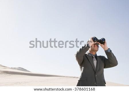 Businessman in desert with binoculars - stock photo