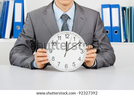 Businessman in elegant suit hold clock, sitting at the desk at office - stock photo