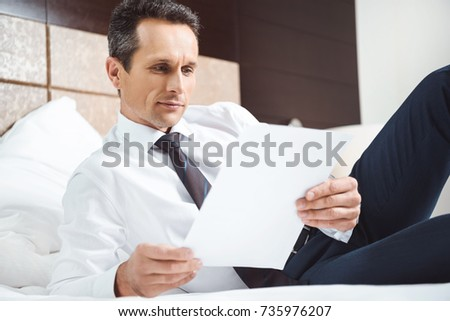 Businessman in formal wear lying on bed in hotel room and reading some paperwork