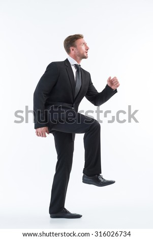 Businessman in formal wear walking up imaginative stairs isolated on white. Serious man looking up and see his aim.