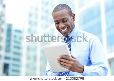 Businessman in formals using tablet device - stock photo