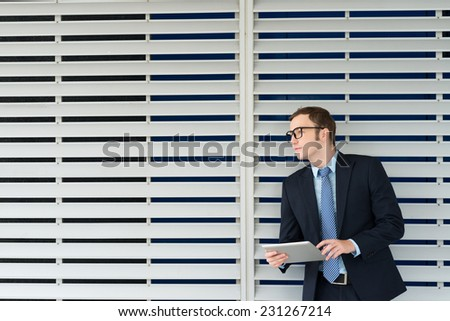 Businessman in formalwear and glasses working on digital tablet - stock photo