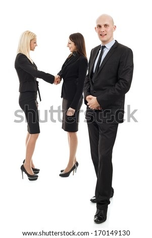Businessman in front and two business women shaking hands in the background out of focus - stock photo