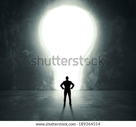 Businessman in front of a bright lightbulb door - stock photo