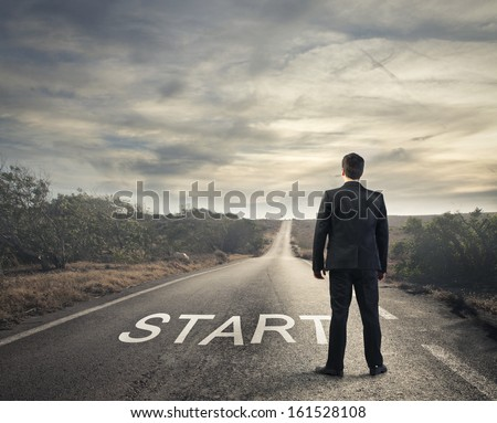 businessman in front of a deserted road - stock photo