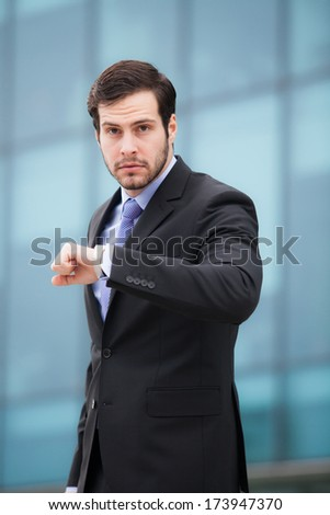 businessman in front of an office building stressed by time
