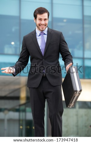businessman in front of an office building with a briefcase   - stock photo