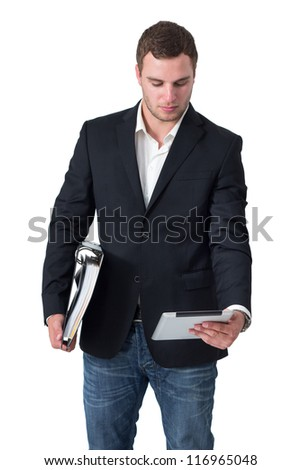 Businessman in front of isolated background looking at tablet pc and holding ring binder - stock photo
