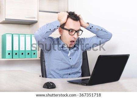 Businessman in front of laptop receiving negative news, pulling hair being mad, upset and surprised. - stock photo