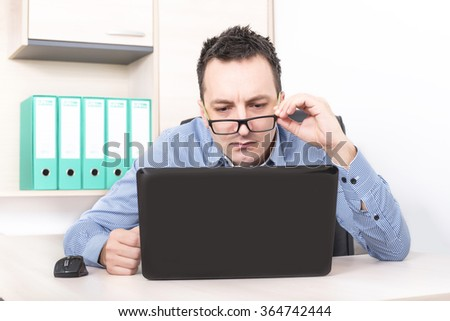 Businessman in front of laptop staring and being curious - stock photo