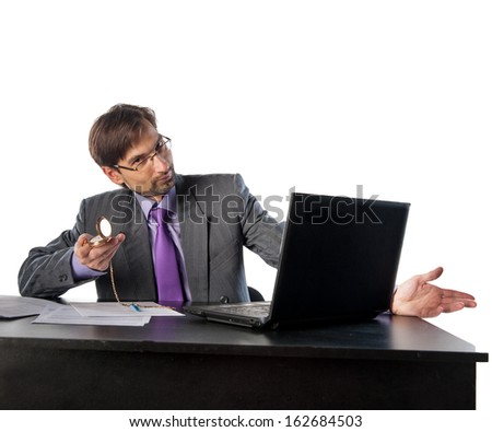 businessman in glasses behind a desk in an office with a clock in his hands