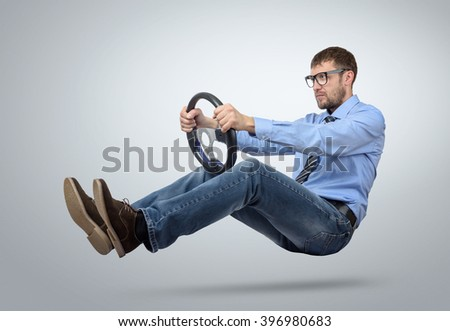 Businessman in glasses car driver with a steering wheel
