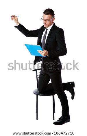 Businessman in glasses writes with pen at copyspace over white background - stock photo