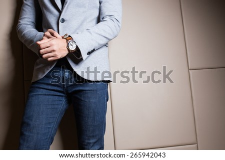Businessman in gray suite,Blue jeans. Part of body. On beige color background