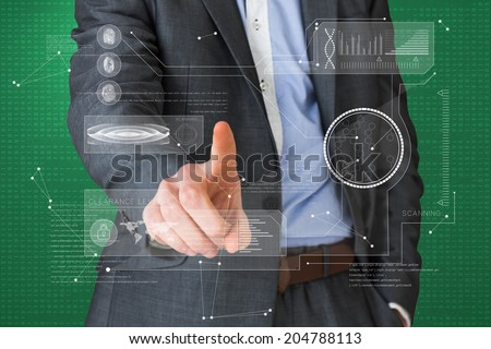 Businessman in grey suit pointing at interface against green vignette
