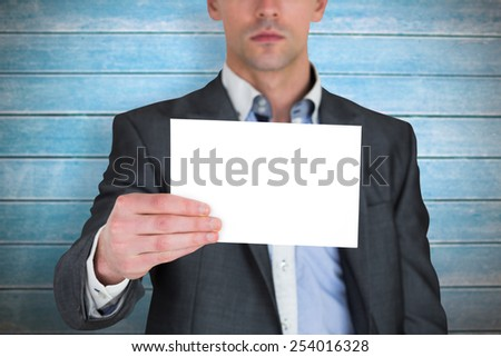 Businessman in grey suit showing card against wooden planks - stock photo