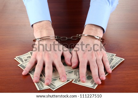 Businessman in handcuffs counts the money for bribes - stock photo