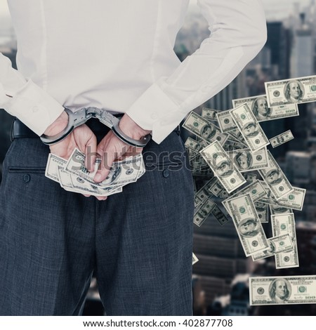 Businessman in handcuffs holding bribe against view of cityscape - stock photo