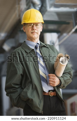 Businessman in hard hat carrying blueprints - stock photo