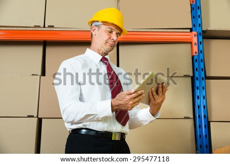 Businessman In Hardhat Looking At Digital Tablet In Warehouse - stock photo