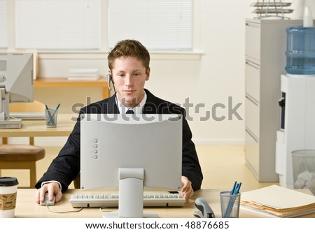 Businessman in headset working at computer - stock photo