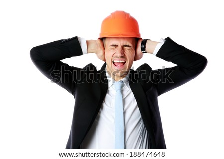Businessman in helmet covering his ears over white background - stock photo