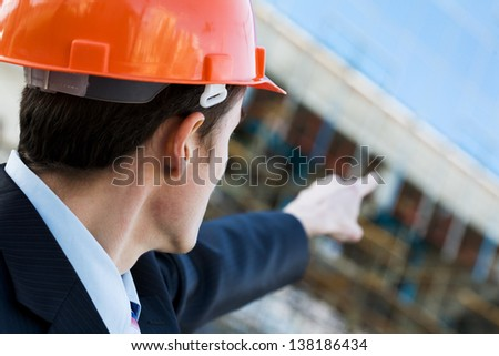 Businessman in helmet showing at office building - stock photo