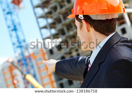Businessman in helmet showing new building - stock photo