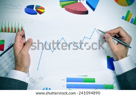 businessman in his office desk full of graphs and charts observing a chart with an upward trend - stock photo