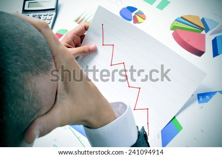 businessman in his office desk full of graphs and charts observing worried a chart with a downward trend - stock photo