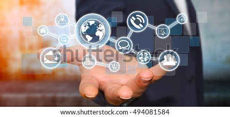 Businessman in his office holding a digital tactile screen web network with web icons 3D rendering