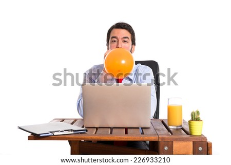 Businessman in his office playing with balloon - stock photo