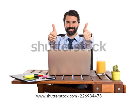 Businessman in his office with thumb up