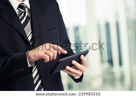 Businessman in his office working on tablet. Toned photo. - stock photo