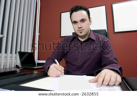 Businessman in his office writing document