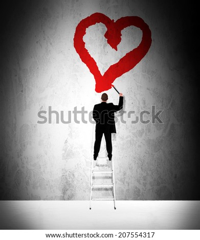 Businessman in love painting a red heart on a grunge wall
