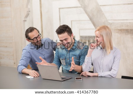 Businessman in middle showing result to his colleagus on laptop computer. Happy smiling people looking at him.