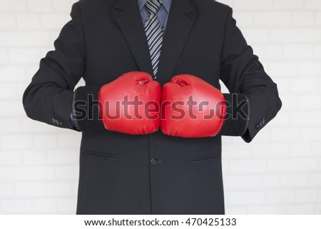 businessman in necktie and suit with red boxing gloves - business competition concept