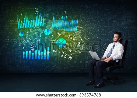 Businessman in office chair with laptop in hand and high tech graph charts concept on background