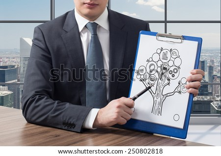 businessman in office holding clipboard with success tree - stock photo