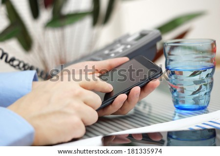 businessman in office is talking on the phone and working with smart phone - stock photo