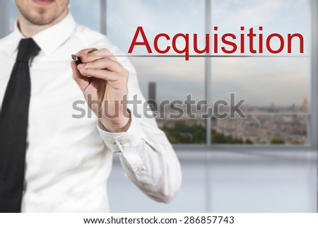 businessman in office room writing accquisition in the air